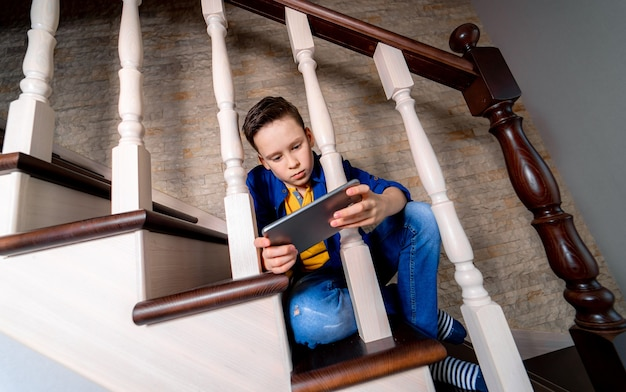 Jonge jongen spelen met smartphone, zittend op de trap. van onderaf bekijken.