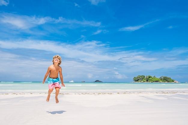 Jonge jongen springen van vreugde op tropisch strand, concept van de zomervakantie