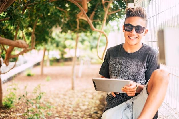 Jonge jongen tiener leeftijd gebruik tablet apparaat buiten in het park glimlachend en genieten van verbindingstechnologie - gelukkige jeugd mensen man portret in natuurtuin