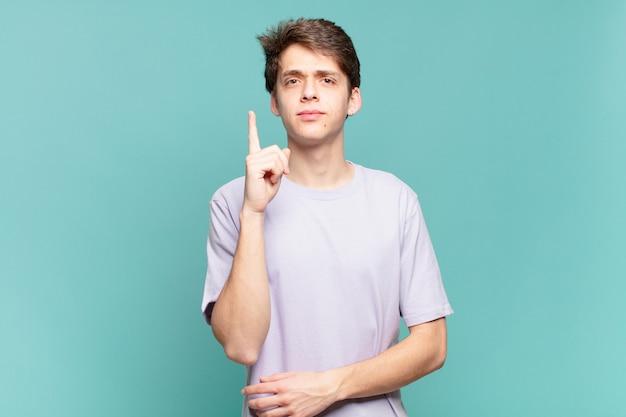 Jonge jongen voelt zich een genie die zijn vinger trots in de lucht houdt nadat hij een geweldig idee heeft gerealiseerd en eureka . zegt