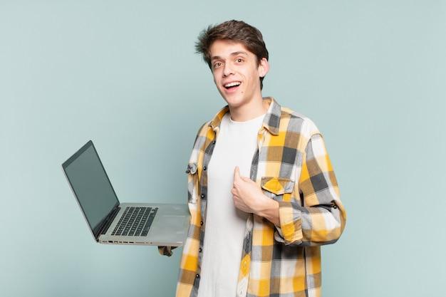 Jonge jongen voelt zich gelukkig, verrast en trots, wijzend naar zichzelf met een opgewonden, verbaasde blik. laptopconcept