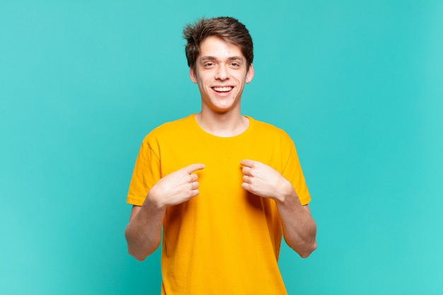 Jonge jongen voelt zich gelukkig, verrast en trots, wijzend naar zichzelf met een opgewonden, verbaasde blik