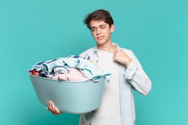 Jonge jongen voelt zich gestrest, angstig, moe en gefrustreerd, trekt aan de nek van het shirt, ziet er gefrustreerd uit met het concept van het wassen van kleding
