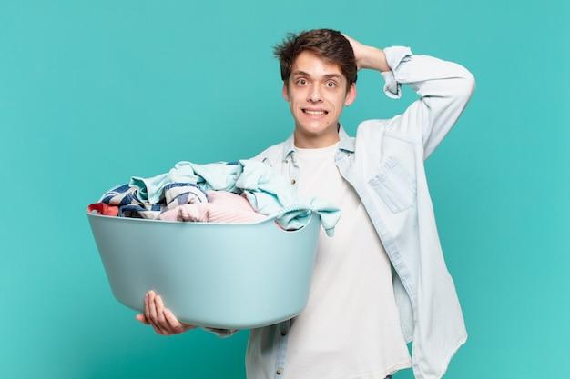 Jonge jongen voelt zich gestrest, bezorgd, angstig of bang, met de handen op het hoofd, in paniek bij het wassen van kledingconcept