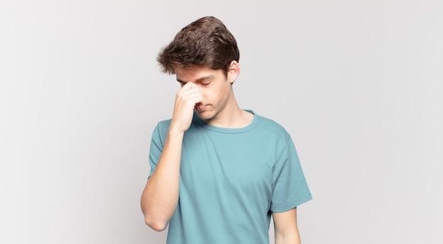 Jonge jongen voelt zich gestrest, ongelukkig en gefrustreerd, raakt het voorhoofd aan en lijdt aan migraine of ernstige hoofdpijn