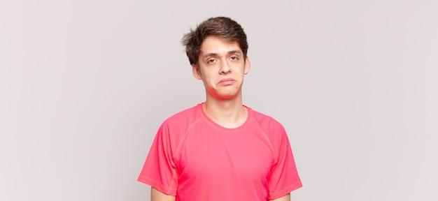 Jonge jongen voelt zich verdrietig en zeurt met een ongelukkige blik, huilt met een negatieve en gefrustreerde houding