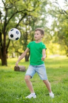 Jonge jongen voetballen in park