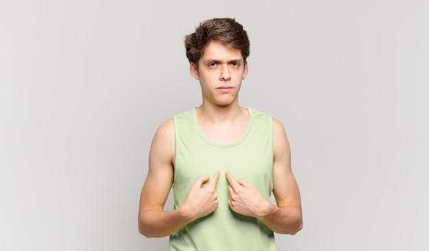 Jonge jongen wijst naar zichzelf met een verwarde en vragende blik, geschokt en verrast om gekozen te worden