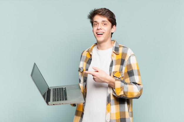 Jonge jongen ziet er opgewonden en verrast uit en wijst naar de zijkant en naar boven om de ruimte te kopiëren. laptopconcept