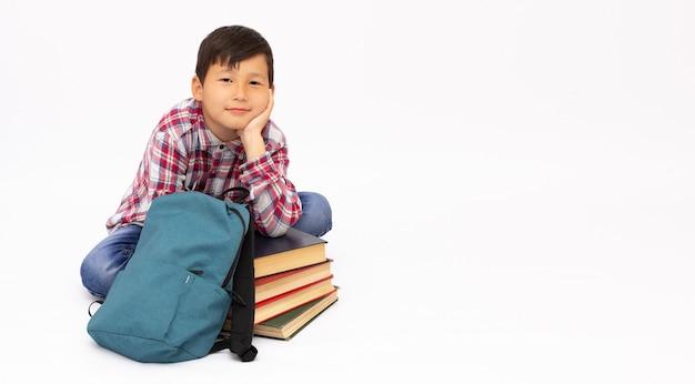 Jonge jongen zit met een stapel boeken en rugzak op wit