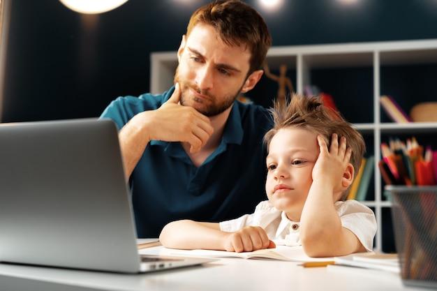 Jonge jongen zit met zijn vader aan de tafel en laptop gebruikt voor studie