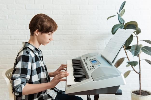 Jonge jongen zit op digitale piano