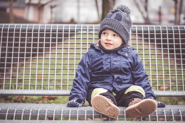 Jonge jongen zittend op de bank