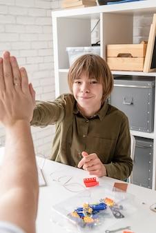 Jonge jongens en leraar hebben plezier bij het bouwen van robotauto's in de werkplaats en geven elkaar een high five