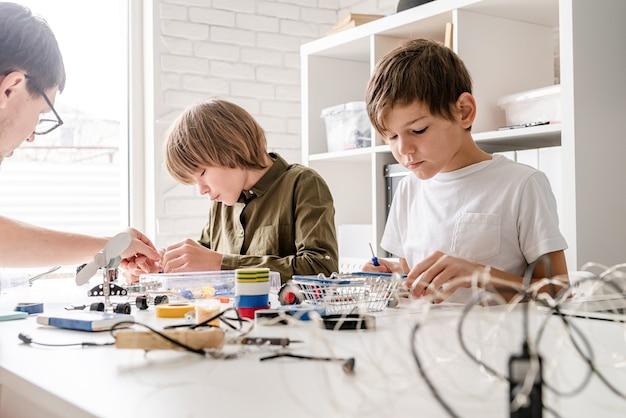 Jonge jongens en leraar plezier samen bouwen van robotauto's in de werkplaats