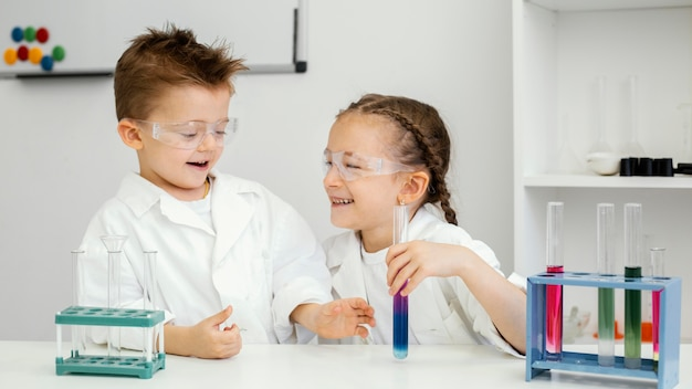 Jonge jongens en meisjeswetenschappers die experimenten in het laboratorium doen en plezier hebben