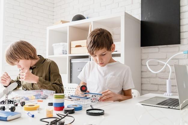 Jonge jongens en plezier hebben bij het samen bouwen van robotauto's in de werkplaats