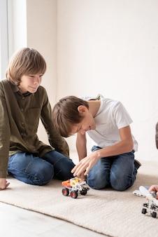Jonge jongens en plezier hebben bij het samen bouwen van robotauto's op het tapijt