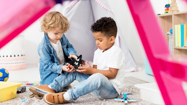 Jonge jongens in tent die thuis met speelgoed spelen