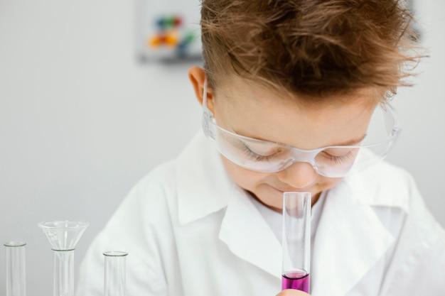 Jonge jongenswetenschapper die experimenten in het laboratorium doet terwijl hij veiligheidsbril draagt