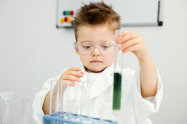 Jonge jongenswetenschapper die experimenten in het laboratorium doet