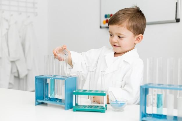 Jonge jongenswetenschapper met reageerbuizen