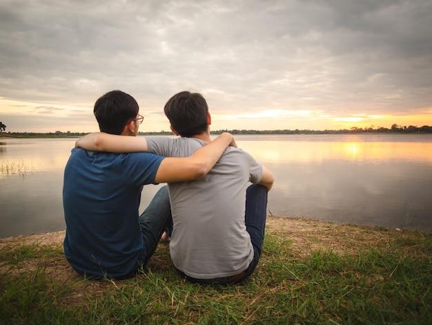Jonge jongenszitting naast het meer en het letten van de op zonsondergang. vriendschap concept.