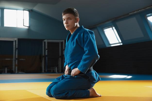 Jonge judo-kaukasische vechter in blauwe kimono met zwarte gordel die zelfverzekerd in de sportschool staat, sterk en gezond. vechtvaardigheden in vechtsporten oefenen. overwinnen, doel bereiken, zelfopbouw.