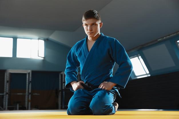 Jonge judo-kaukasische vechter in blauwe kimono met zwarte gordel die zelfverzekerd in de sportschool staat, sterk en gezond.