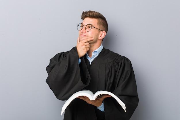 Jonge jurist die een boek houdt dat opzij kijkt met twijfelachtige en sceptische uitdrukking.