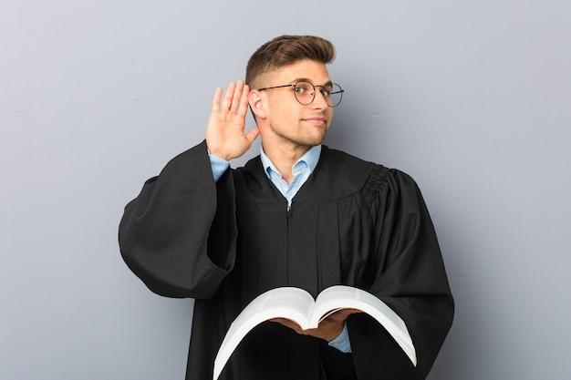 Jonge jurist die een boek houdt dat probeert aan het luisteren van een roddel.