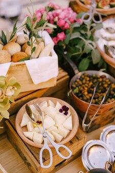 Jonge kaas met broodjes en gevulde olijven op een tafel met bloempotten