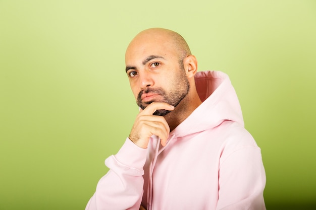 Jonge kale blanke man in roze hoodie geïsoleerd, bezorgd over een vraag, bezorgd en nerveus met de hand op de kin