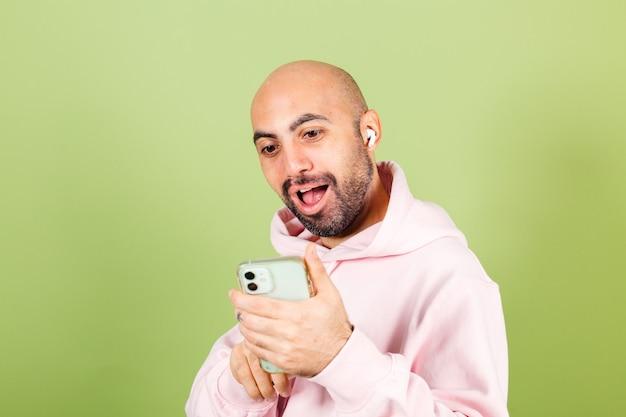 Jonge kale blanke man in roze hoodie geïsoleerd, houd telefoon blik op het scherm met verbaasd geschokt gezicht