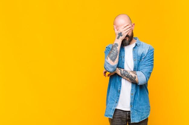 Jonge kale en bebaarde man die gestrest, beschaamd of boos kijkt, met hoofdpijn, gezicht bedekt met hand