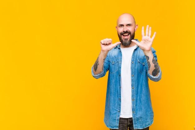 Jonge kale en bebaarde man die vriendelijk glimlacht en kijkt, nummer zes of zesde met vooruit hand toont, aftellend