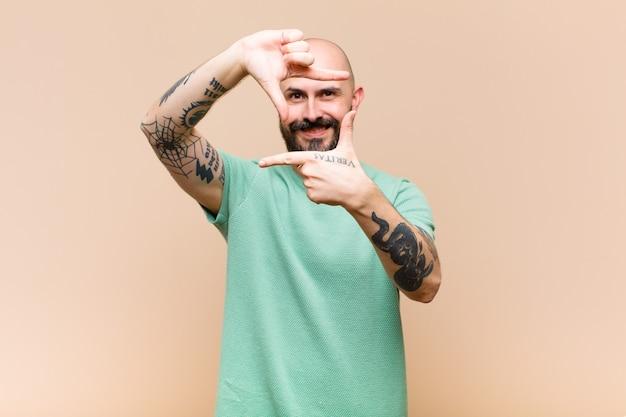 Jonge kale en bebaarde man die zich gelukkig, vriendelijk en positief voelt, lacht en een portret of fotolijst met handen maakt