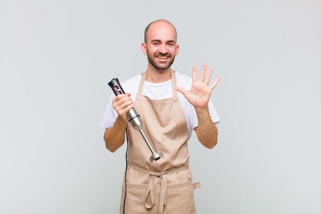Jonge kale en mens die vriendelijk glimlacht kijkt, nummer vijf of vijfde met vooruit hand toont, aftellend