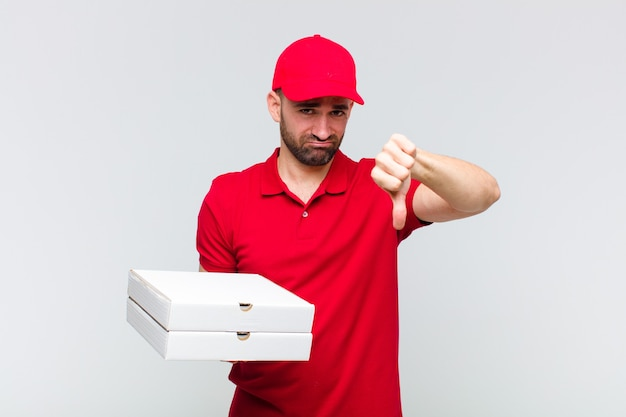 Jonge kale man die boos, boos, geïrriteerd, teleurgesteld of ontevreden voelt, duimen naar beneden toont met een serieuze blik