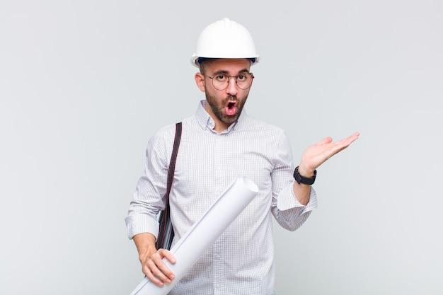 Jonge kale man die verbaasd en geschokt kijkt, met open mond een voorwerp vasthoudend met een open hand op de zijkant