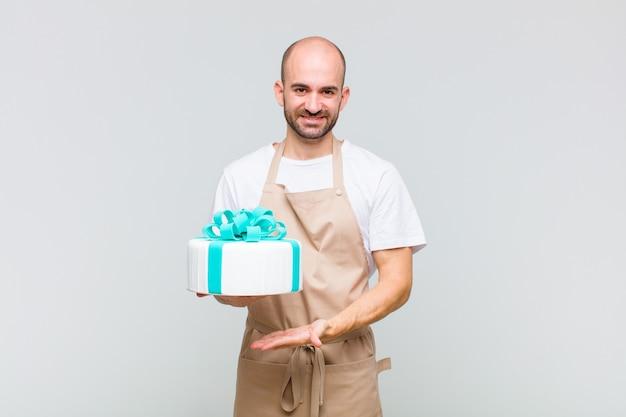 Jonge kale man die vrolijk glimlacht, zich gelukkig voelt en een concept in exemplaarruimte met handpalm toont