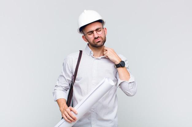 Jonge kale man die zich gestrest, angstig, moe en gefrustreerd voelt, aan de hals van het shirt trekt, gefrustreerd kijkt door het probleem