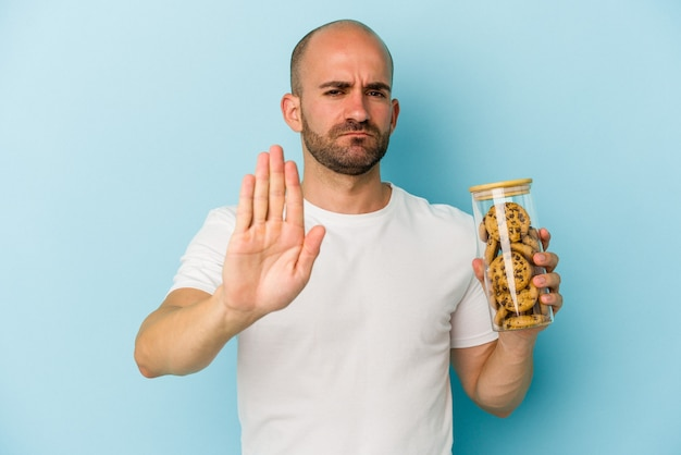 Jonge kale man met cookies geïsoleerd op blauwe achtergrond staande met uitgestrekte hand weergegeven: stopbord, waardoor u.