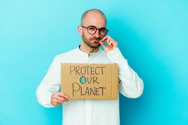Jonge kale man met een bescherm onze planeet aanplakbiljet geïsoleerde muur met vingers op lippen die een geheim houden