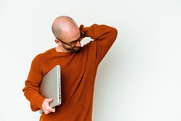 Jonge kale man met een laptop geïsoleerd op een witte muur achterkant van het hoofd aanraken, denken en een keuze maken.