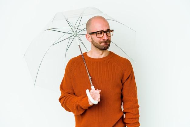 Jonge kale man met een paraplu geïsoleerd verward, twijfelachtig en onzeker.