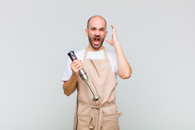 Jonge kale man schreeuwen met de handen in de lucht, woedend, gefrustreerd, gestrest en boos