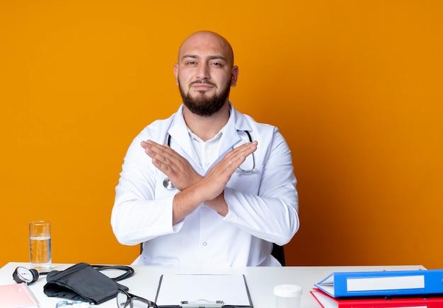 Jonge kale mannelijke arts die medische robe en stethoscoopzitting aan bureau met medische hulpmiddelen draagt die gebaar van geen toont dat op oranje achtergrond wordt geïsoleerd