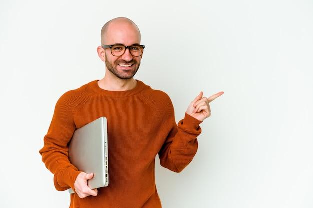 Jonge kale mens die laptop houdt die op witte muur wordt geïsoleerd die en opzij glimlacht richt, die iets op lege ruimte toont.