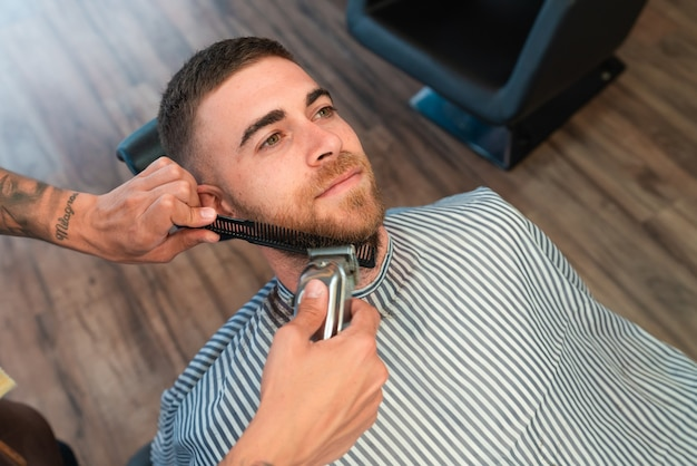 Jonge kapper die de baard van de mannelijke klant scheert met een kam en een tondeuse in een kapperszaak